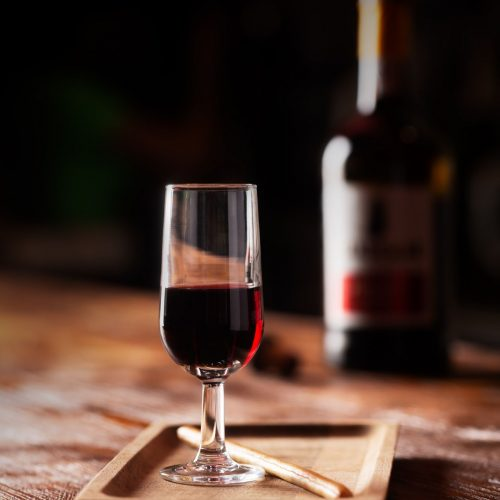 Glass of Port Wine on Wooden Table Over Dark Background